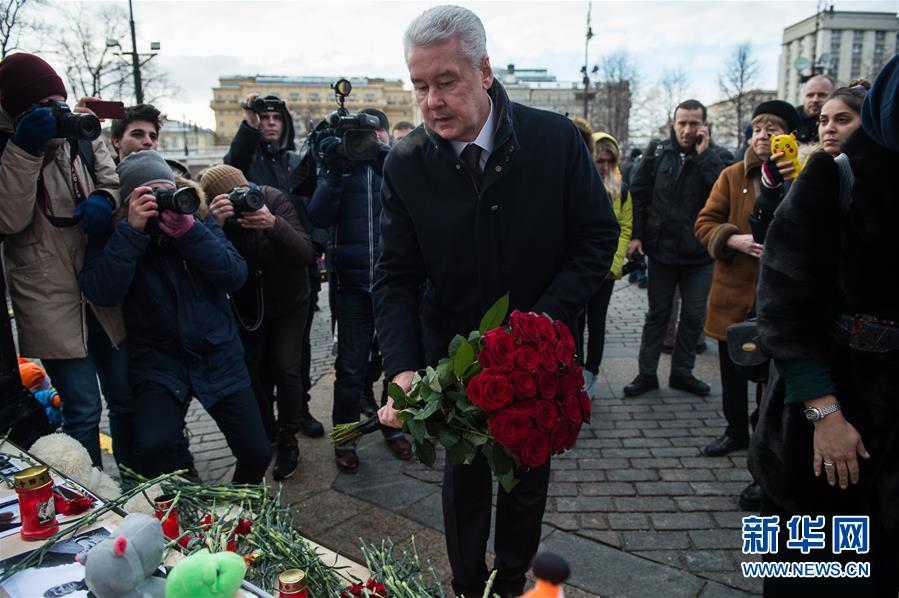3月27日,在俄罗斯首都莫斯科,莫斯科市长索比亚宁(中)摆放鲜花悼念克麦罗沃火灾遇难者。