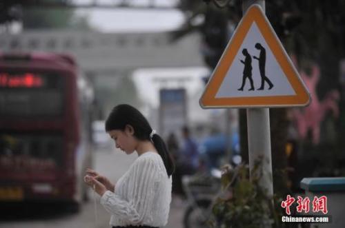 """资料图:重庆一红绿灯处摆放""""不做低头族、关注红绿灯""""警示牌,提醒市民在过斑马线的时候不能玩手机。 陈超 摄"""